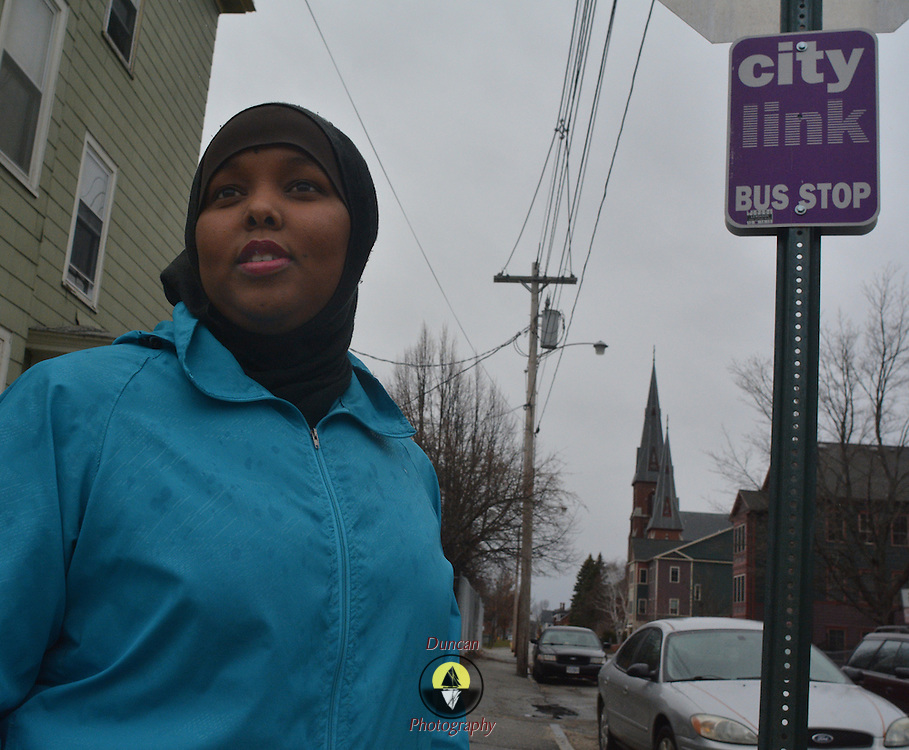 LEWISTON, Maine,  -- 4/2/16 --  Fahmo Ahmed, 28, stands at a bus stop near her home in Lewiston where she has repeatedly been verbally accosted -- called a terrorist -- by passersby. She came to the United States from Somalia 12 years ago, graduated from Edward Little, earned her citizenship and working her way towards graduation from college this year. A vibrant community organizer and advocate for women's reproductive rights, she hopes someday to run for office. Photo by Roger S. Duncan for The Forecaster