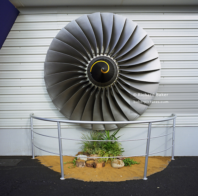 A Rolls-Royce turbofan has been fixed to the exterior of the company?s sales stand at the Farnborough Air Show in Hampshire, England. The British-owned company have been making aircraft engines since 1914 at the start of the First World War, in response to the nation's needs, Royce designed his first aero engine ? the Eagle. Modern airliners have the Trent engine's technology embedded in its power plants and Farnborough is a major showcase for its many designs. Here, their chalet has a mocked-up garden feature complete railings and the turbine blades attached to the wall above. Picture from the 'Plane Pictures' project, a celebration of aviation aesthetics and flying culture, 100 years after the Wright brothers first 12 seconds/120 feet powered flight at Kitty Hawk,1903. .