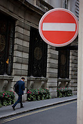 A city worker strides up a narrow street, aginst the flow of traffic as described by the No Entry sign in the City of London.