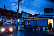 Nighttime scene outside an eatery on an intersection in San Cristobal de las Casas, Chiapas, Mexico on June 24, 2008. A flashy red Volkswagen sports car drives past, in stark contrast to the drab surroundings and the pedestrians and bicycle rider.