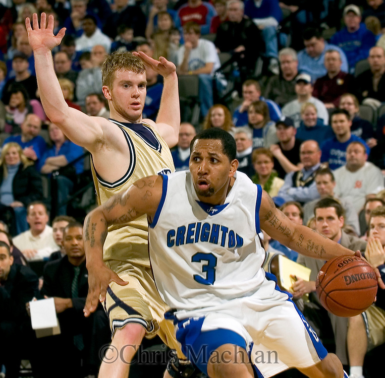 3/16/06 -- Omaha, ne  Creighton's Nick Porter drives the ball past Akron's Nick  DIALS in the first round game of the NIT at Qwest Center Omaha. (Photo by Chris Machian/Prairie Pixel Group).