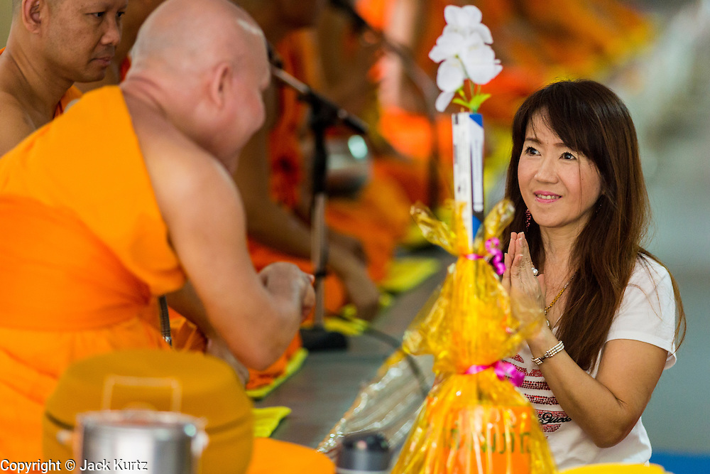 """22 JULY 2013 - PHRA PHUTTHABAT, THAILAND:  A monk receives an offering from an woman during the Tak Bat Dok Mai at Wat Phra Phutthabat in Saraburi province of Thailand, Monday, July 22. Wat Phra Phutthabat is famous for the way it marks the beginning of Vassa, the three-month annual retreat observed by Theravada monks and nuns. The temple is highly revered in Thailand because it houses a footstep of the Buddha. On the first day of Vassa (or Buddhist Lent) people come to the temple to """"make merit"""" and present the monks there with dancing lady ginger flowers, which only bloom in the weeks leading up Vassa. They also present monks with candles and wash their feet. During Vassa, monks and nuns remain inside monasteries and temple grounds, devoting their time to intensive meditation and study. Laypeople support the monastic sangha by bringing food, candles and other offerings to temples. Laypeople also often observe Vassa by giving up something, such as smoking or eating meat. For this reason, westerners sometimes call Vassa the """"Buddhist Lent.""""    PHOTO BY JACK KURTZ"""
