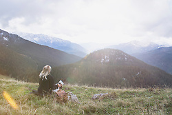 Young woman sitting with dog in the mountain, Bavaria, Germany