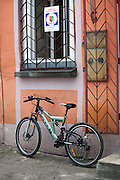 High - tech modern bicycle beneath a barred window and entrance with a security sign. Tomaszow Mazowiecki Central Poland