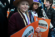 March 4th 2017. Thousands of people, mostly women and girls, marched across Tower Bridge in an event organised by Care International to mark International Womens Day March 8th and the need for gender equality. Two girls dressed in suffragette period clothing hold signs saying March for women.