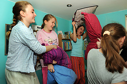 Teenage girls have a pillow fight at a sleepover