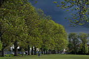 The dark skies of an approaching rain storm approach park users in Ruskin Park in Lambeth, south London, on 24th May 2021, in London, England.