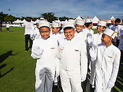 "28 AUGUST 2014 - BANGKOK, THAILAND: Thai children in the bellhop uniforms on the Peninsula Hotel at the opening ceremony of the King's Cup Elephant Polo Tournament at VR Sports Club in Samut Prakan on the outskirts of Bangkok, Thailand. The tournament's primary sponsor in Anantara Resorts. This is the 13th year for the King's Cup Elephant Polo Tournament. The sport of elephant polo started in Nepal in 1982. Proceeds from the King's Cup tournament goes to help rehabilitate elephants rescued from abuse. Each team has three players and three elephants. Matches take place on a pitch (field) 80 meters by 48 meters using standard polo balls. The game is divided into two 7 minute ""chukkas"" or halves.    PHOTO BY JACK KURTZ"