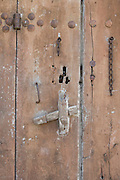 close up of an old wooden door with handle and broken chain