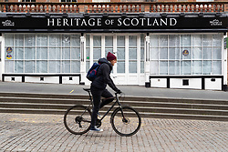 Edinburgh, Scotland, UK. 18 April 2020. Views of empty streets and members of the public outside on another Saturday during the coronavirus lockdown in Edinburgh. Man cycles past closed tourist souvenir shop on the Royal Mile. Iain Masterton/Alamy Live News