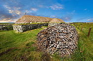 Picture & image peat pile oustide the exterior with stone walls and thatched roof of The historic Blackhouse, 24 Arnol, Bragar, Isle of Lewis, Scotland. .<br /> <br /> Visit our SCOTLAND HISTORIC PLACXES PHOTO COLLECTIONS for more photos to download or buy as wall art prints https://funkystock.photoshelter.com/gallery-collection/Images-of-Scotland-Scotish-Historic-Places-Pictures-Photos/C0000eJg00xiv_iQ