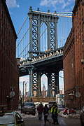 The Empire State Building framed by the Manhattan Bridge structure, as seen from Washington Street, Dumbo, New York City, United States of America.  People walk across the street, which still has cars surrounded in snow.