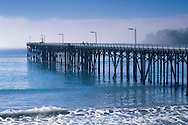 Coastal fogbank offshore from wooden pier and wave Wm R. Hearst State Beach, San Simeon, California