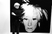 Portraits of Andy Warhol at the opening of the exhibition Andy Warhol, Anthony d'Offay Gallery, London, 1986. A rare masterpiece completed just months before Andy Warhol's sudden death in 1987. Andy Warhol seen with one of his 22x22-inch canvas iconic self-portraits-the first and only self-portrait exhibition of Warhol's career. Works from this exhibition now hang in the collections of the Tate London, the Metropolitan Museum of Art, New York and the Carnegie Museum of Art, Pittsburgh.