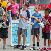Four kids look on curiously at a spin the wheel challenge at Appalachian Power Park in Charleston, W.V. on Tuesday, July 17, 2018.