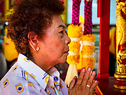 """02 JUNE 2017 - SAMUT SAKHON, THAILAND: A woman prays before the City Pillar Shrine parade in Samut Sakhon. The Chaopho Lak Mueang Procession (City Pillar Shrine Procession) is a religious festival that takes place in June in front of city hall in Samut Sakhon. The """"Chaopho Lak Mueang"""" is  placed on a fishing boat and taken across the Tha Chin River from Talat Maha Chai to Tha Chalom in the area of Wat Suwannaram and then paraded through the community before returning to the temple in Samut Sakhon. Samut Sakhon is always known by its historic name of Mahachai.      PHOTO BY JACK KURTZ"""