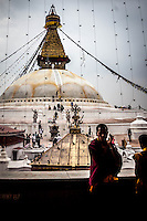 Monks chat on a monastery balcony overlooking the Boudhanath Stupa, Nepal.