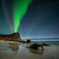 Northern Lights fill sky over Myrland beach, Flakstadoy, Lofoten Islands, Norway
