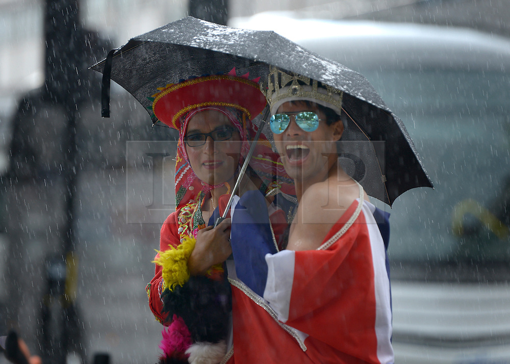 © Licensed to London News Pictures. 07/07/2012. London, UK Guests at the World Pride Procession shelter from the rain in Central London today 7th July 2012. Despite reports of it's cancellation due to financial difficulty the scaled-down event went ahead after changes to its schedule. Photo credit : Stephen Simpson/LNP