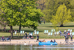 Licensed to London News Pictures. 02/05/2021. London, UK. Sunshine and showers for members of the public as they relax and enjoy the Bank Holiday weekend along the Serpentine in Hyde Park, London ahead of tomorrow's Bank Holiday Monday with weather experts predicting high winds and driving rain with a high of 10c. Today, Health Secretary Dominic Rabb admits that masks could be with us for the summer as virtually all social restrictions will be lifted by June 21 2021. Photo credit: Alex Lentati/LNP