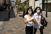 As the national coronavirus lockdown three eases towards the planned Freedom Day in just over two weeks, people, many of whom are still wearing face masks while out on the street, come to Covent Garden on 2nd July 2021 in London, United Kingdom. Now that the roadmap for coming out of the national lockdown and easing of restrictions is set, dome medical professionals are suggesting thatsome safety measures are kept in place because of the increase in the Delta variant.