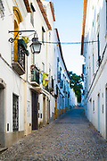 Typical street scene of white and yellow houses, lanterns and narrow cobble street in Evora, Portugal
