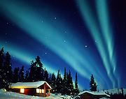 Remote cabin in Alaska is illuminated by the Northern Lights
