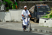 Pemangku, or local priest, on bicycle. Sanur, Bali, Indonesia