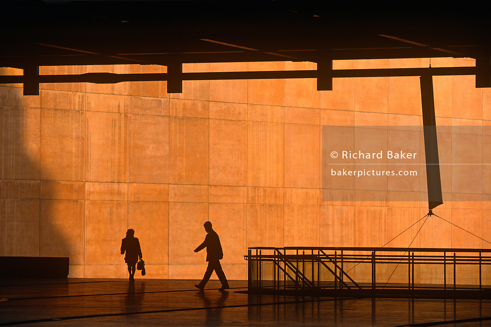 We see four office workers silhouetted against the large orange wall of the Credit Lyonnais Bank at Broadgate in the City of London, UK. Several figures who are also reduced to black shapes and without detail that may identify them or their clothes, are hurrying in different directions, carrying a bag or briefcase but the feeling of rushing business is seen and their scale is ambiguous becase we don't know how close or far away they are from each other. This is due to telephoto lens forshortening. Some therefore look giants and some appear tiny. Broadgate Estate is a large, 32 acre (129,000 m²) office and retail estate in the City of London, owned by British Land and managed by Broadgate Estates. It was originally built by Rosehaugh and was the largest office development in London until the arrival of Canary Wharf in the early 1990s.