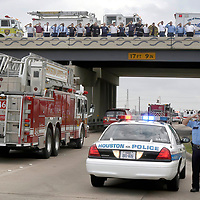 Firefighters from Nassau Bay, Webster Forest Bend League City Fire Departments, Nassau Bay EMS and HPD Police Officer lined the NASA Bridge over I-45 as fallen firefighter Capt. Grady Burke, 39, passes under on the way to the funeral home in Webster, 02/20/04.  Burke died Saturday morning when he became trapped under a collapsed roof of a burning home..  (Photo by Kim Christensen)