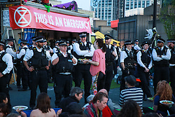 London, UK. 20th April 2019. A climate change activist offers free vegan food to police officers who had come to reclaim Waterloo bridge, which has been blocked for six days, from Extinction Rebellion.