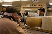 A cheese vendor at Alex Farm Products gestures from behind a wheel of Parmigiano-Reggiano at Toronto's St. Lawrence Market.