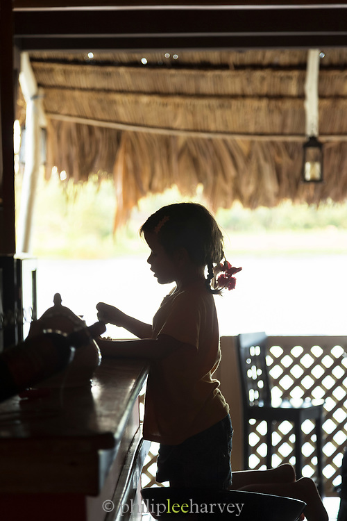 Silhouette of a young girl inside of a house in the town of El Castillo, Rio San Juan Department, Nicaragua