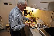 elderly man making a sandwich
