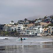 A man with a kayak near beach front homes in Malibu, California.