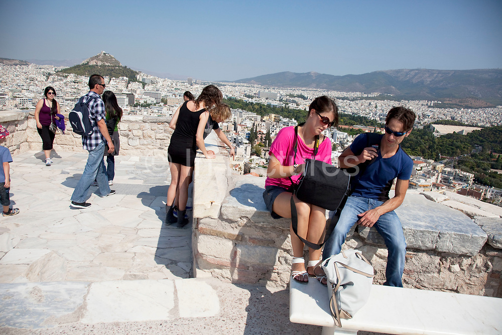 Tourists and visitors at the Acropolis of Athens. Athens with views down from the top of the hill across Athens, the capital and largest city of Greece. It dominates the Attica periphery and is one of the world's oldest cities, as its recorded history spans around 3,400 years. Classical Athens was a powerful city-state. A centre for the arts, learning and philosophy.