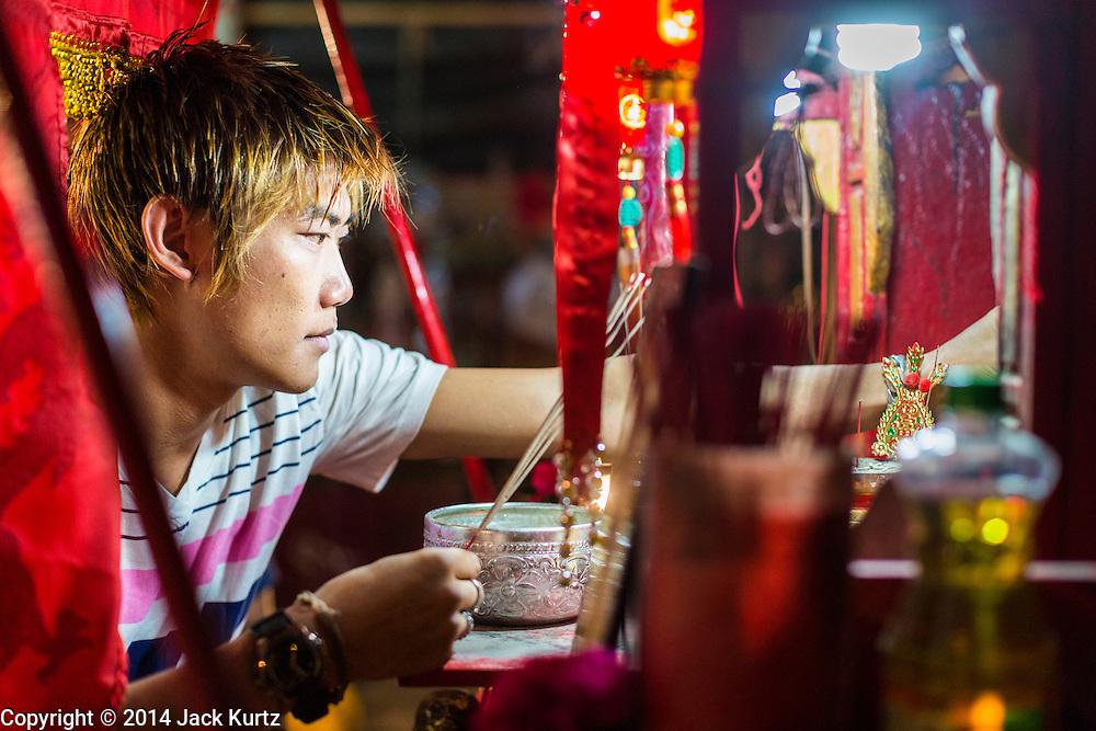 "25 JANUARY 2014 - BANG LUANG, NAKHON PATHOM, THAILAND: A performer with the Sing Tong Teochew opera troupe prays at a Chinese alter backstage before a show in a Chinese shrine in the town of Bang Luang, Nakhon Pathom, Thailand. The Sing Tong Teochew opera troupe has been together for 60 years and travels through central Thailand and Bangkok performing for mostly ethnic Chinese audiences. Chinese opera was once very popular in Thailand, where it is called ""Ngiew."" It is usually performed in the Teochew language. Millions of Chinese emigrated to Thailand (then Siam) in the 18th and 19th centuries and brought their cultural practices with them. Recently the popularity of ngiew has faded as people turn to performances of opera on DVD or movies. There are still as many 30 Chinese opera troupes left in Bangkok and its environs. They are especially busy during Chinese New Year when travel from Chinese temple to Chinese temple performing on stages they put up in streets near the temple, sometimes sleeping on hammocks they sling under their stage.     PHOTO BY JACK KURTZ"