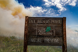 Smoke filled sky and Matthews Prairie sign after controlled burn on the Matthews Prairie, owned by the Native Prairies Association of Texas. Farmersville, Texas, USA.