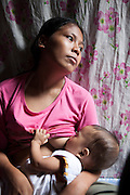 Vilma Tacuyo, 20, breastfeeds her youngest child, Ulderico (10 months), in their one room home in an urban slum in Paranaque City, Metro Manila, The Philippines on 18 January 2013. Vilma had raised her first 3 children on formula and had to cut down on food for her family to afford it. Both John Ashley, 4, and Justin, 3, are malnourished and stunted, and after losing one of her children, she now breastfeeds her youngest, Ulderico. Photo by Suzanne Lee for Save the Children UK