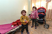 """Veronica's children standing in the living room on Tuesday, Dec 28, 2020. Their Mom said that they will not return to Nagorno Karabakh. The family is now looking for opportunities to work and live in Armenia. They're now under Armenian government logistics support for food, shelter and other essential supplies. The family is living at an abandoned building of former """"SOVIET Hotel"""" in Metsamor, which is located near the Armenian Nuclear Power Plant, that is the only nuclear power plant in the South Caucasus, located 36 kilometres west of Yerevan in Armenia. (Photo/ Vudi Xhymshiti)"""