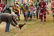 A home owner releases a live chicken as revelers prepare to pounce during the Faquetigue Courir de Mardi Gras chicken run on Fat Tuesday February 17, 2015 in Eunice, Louisiana. The traditional Cajun Mardi Gras involves costumed revelers competing to catch a live chicken as they move from house to house throughout the rural community.