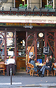 Le Bistrot du Peintre cafe bar terrasse terasse outside seating on the sidewalk. People sitting in chairs at tables eating and drinking outside at lunch time The Bistrot du Peintre is an old fashioned Paris café cafe bar restaurant of art nouveau design with polished brass, mirrors and old signs