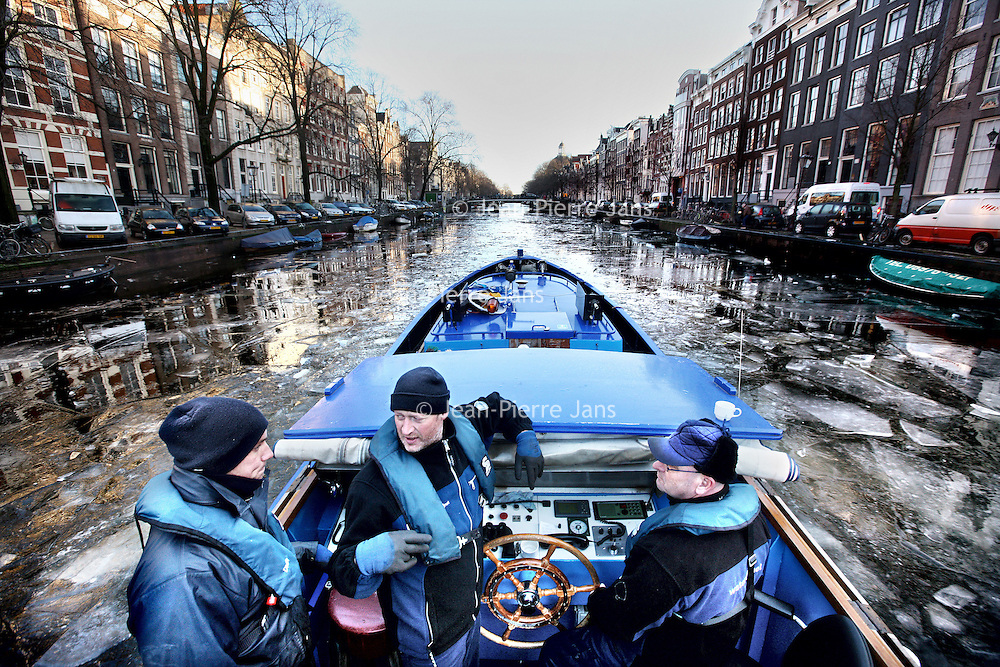 Nederland, Amsterdam , 28 januari 2013..v.l.n.r. Tom, Ruud en Hennie op hun IJsbreker door de Amsterdamse grachten..Three men on their ice-breaker breaking the ice of the Amsterdam canals.