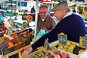 Frenchmen working  on fruit staff at food market at Esplanade  des Quais in La Reole, Bordeaux region, France