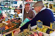 Frenchmen working  on fruit staff at food market at Esplanade  des Quais in La Reole, Bordeaux region, France