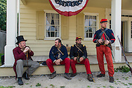"""Old Bethpage, New York, USA. August 30, 2015. L-R in soldier uniforms, SEAN SULLIVAN from Greenlawn, ANDRES PREBLE from Long Beach, and MATT DELLINGER from Brooklyn, portray American Civil War soldiers from the 14th Brooklyn Regiment (14th New York State Militia) AKA The Brooklyn Chasseurs, at the Noon Inn tavern during the Old Time Music Weekend at the Old Bethpage Village Restoration. During their historical reenactments, m embers of the non-profit 14th Brooklyn Company E wear accurate reproductions of """"The """"Red Legged Devils"""" original Union army uniform."""