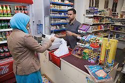 Woman paying for shopping at shop till,