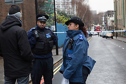 © Licensed to London News Pictures. 03/01/2015. London, UK. Police Community Support Officers speak to a local resident at the top of the police cordon near Stelfox House in Penton Rise. Police have launched a murder investigation after two men were found dead following a suspicious house fire in Penton Rise in Islington, north London last night. Photo credit : Vickie Flores/LNP