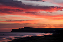 © Licensed to London News Pictures. 25/01/16<br /> Marske-by-the-Sea, UK. <br /> <br /> Viewed from Marske by the Sea the sky turns red over cliffs  near Saltburn as the sun begins to rise.<br /> Remnants of Storm Jonah are expected to bring weather disruption to parts of the country over the next few days.<br /> <br /> Photo credit : Ian Forsyth/LNP
