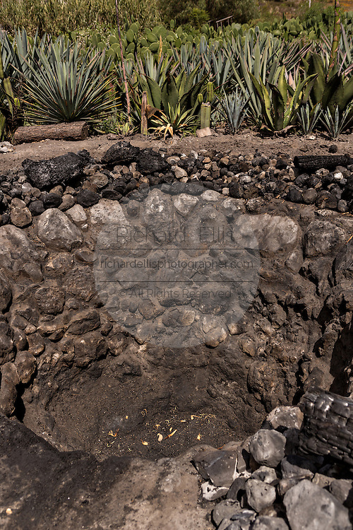 A stone roasting pit where blue agave hearts are roasted to release their juice at an artisanal Mezcal distillery November 5, 2014 in Matatlan, Mexico. Making Mezcal involves roasting the blue agave, crushing it and then fermenting the liquid.